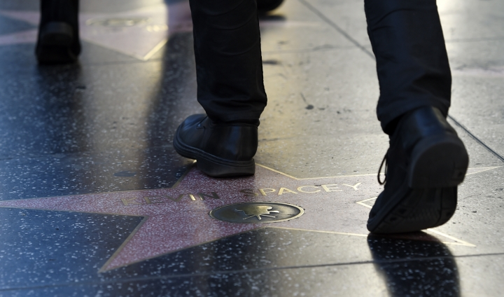 """This Nov. 22, 2017 photo shows a pedestrian walking over the star of actor Kevin Spacey on the Hollywood Walk of Fame in Los Angeles. The ongoing sexual harassment scandals have colored every phase of awards season, but whether they will ultimately shape who wins is another question. Spacey, who was once considered a contender for best supporting actor for his role in Ridley Scott's """"All the Money in the World,"""" was replaced by Christopher Plummer amid sexual misconduct claims. (AP Photo/Chris Pizzello)"""