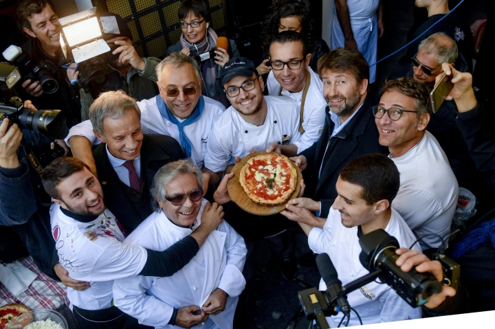 Italian Culture Minister Dario Franceschini, second from right, holds a pizza cooked the in first stone oven which was used in the 1889 to make the first pizza Margherita in Naples, Italy, Wednesday, Dec. 6, 2017. Italy is waiting a decision by the United Nations Educational, Scientific and Cultural Organisation (UNESCO) to recognize to the Neapolitan pizza in the intangible cultural heritage list. (Ciro Fusco/ANSA Via AP)