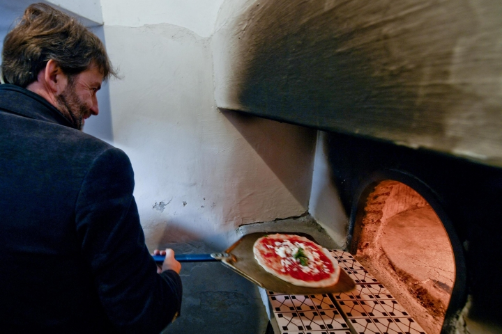 Italian Culture Minister Dario Franceschini cooks a pizza in the first stone oven which was used in the 1889 to make the first pizza Margherita in Naples, Italy, Wednesday, Dec. 6, 2017. Italy is waiting a decision by the United Nations Educational, Scientific and Cultural Organisation (UNESCO) to recognize to the Neapolitan pizza in the intangible cultural heritage list. (Ciro Fusco/ANSA Via AP)