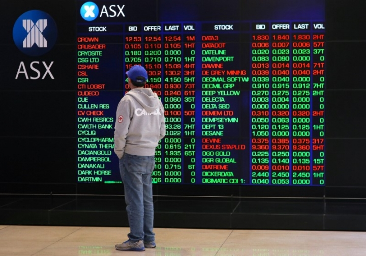 FILE PHOTO - An investor looks at a board displaying stock prices at the Australian Securities Exchange (ASX) in Sydney, Australia, July 17, 2017. REUTERS/Steven Saphore