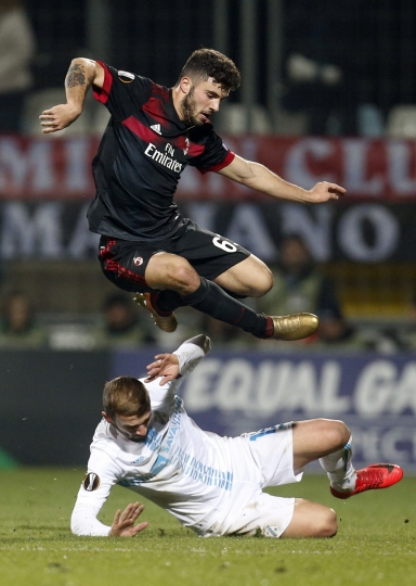 Milan's Patrick Cutrone, top, jumps over Rijeka's Dario Zuparic during the group D Europa League soccer match between Rijeka and Milan, at the Rujevica stadium in Rijeka, Croatia, Thursday, Dec. 7, 2017. (AP Photo/Darko Bandic)
