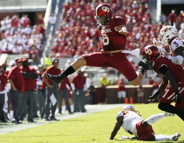 FILE - In this Oct. 7, 2017, file photo, Oklahoma quarterback Baker Mayfield (6) leaps over Iowa State defensive back De'Monte Ruth, bottom, in the second quarter of an NCAA college football game in Norman, Okla. Baker Mayfield is the AP player of the year, becoming the fourth Oklahoma quarterback to win the award since it was established in 1998. (AP Photo/Sue Ogrocki, File)