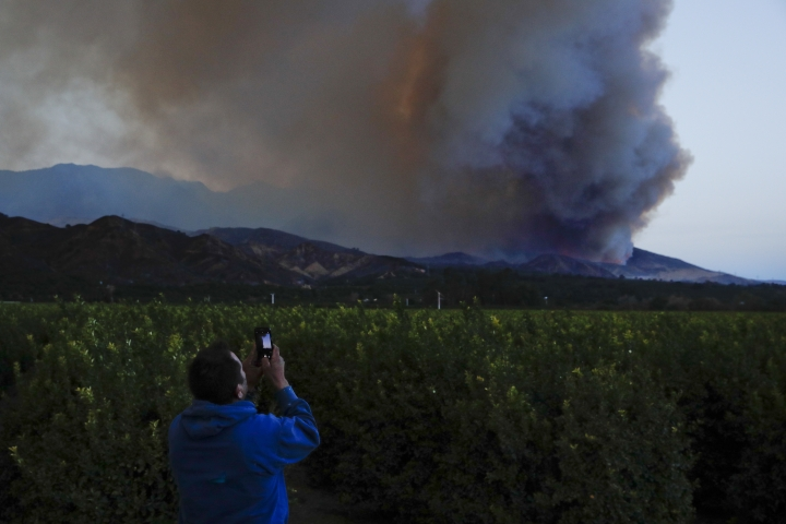 Lupe Robles uses his phone to take pictures of a huge plume of smoke from a wildfire in Santa Paula, Calif., Thursday, Dec. 7, 2017. (AP Photo/Jae C. Hong)