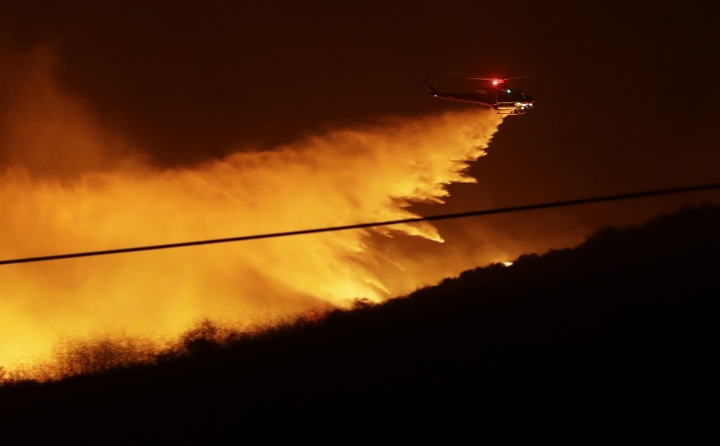 A helicopter drops water on a wildfire Thursday, Dec. 7, 2017, in Bonsall, Calif. The wind-swept blazes have forced tens of thousands of evacuations and destroyed dozens of homes in Southern California. (AP Photo/Gregory Bull)