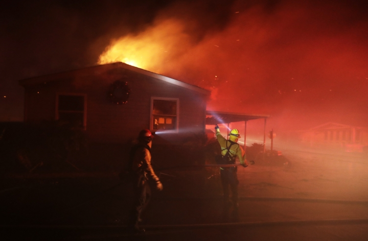 Fire crews work among burning homes at the Rancho Monserate Country Club community Thursday, Dec. 7, 2017, in Fallbrook, Calif. The wind-swept blazes have forced tens of thousands of evacuations and destroyed dozens of homes in Southern California. (AP Photo/Gregory Bull)