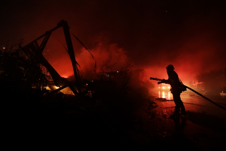 Fire crews work among destroyed homes at the Rancho Monserate Country Club community Thursday, Dec. 7, 2017, in Fallbrook, Calif. The wind-swept blazes have forced tens of thousands of evacuations and destroyed dozens of homes in Southern California. (AP Photo/Gregory Bull)