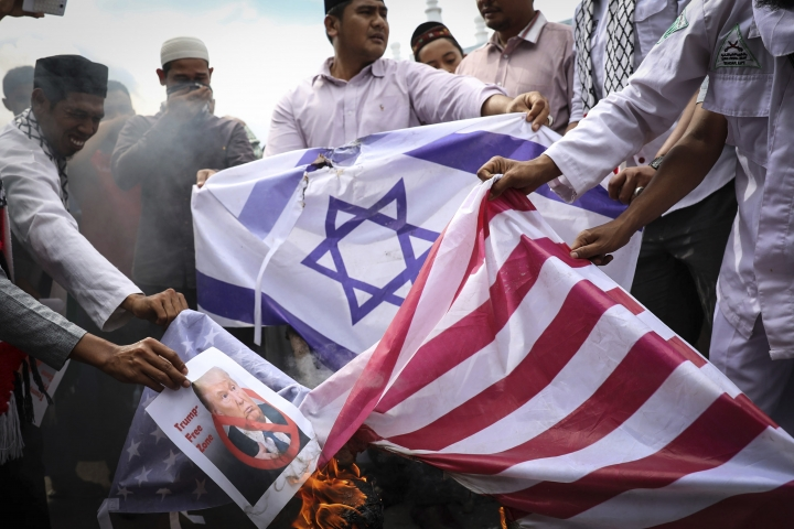 Muslim men burn Israeli and U.S. flags during a protest against the U.S. President Donald Trump's decision to recognize Jerusalem as Israel's capital in Banda Aceh, Indonesia, Friday, Dec. 8, 2017. Hundreds of people across the most populous Muslim country staged protests Friday against Trump administration's policy shift on the contested city. (AP Photo/Heri Juanda)