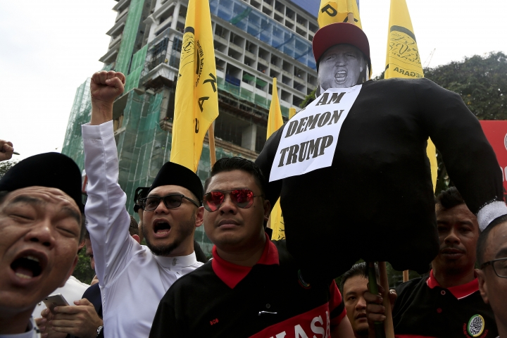 Muslims hold U.S. President Donald Trump's effigy during a protest outside the U.S. Embassy in Kuala Lumpur, Malaysia, Friday, Dec. 8, 2017. Malaysian Muslims, including members of the ruling party, hold protest outside U.S. Embassy over Washington's controversial move to recognize Jerusalem as Israel's capital. (AP Photo/Sadiq Asyraf)