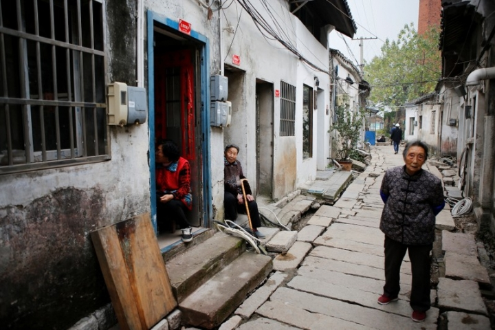 Local residents are seen in an old street in Dingshu town, where local shop owners make and sell handmade red clay tea-ware that is being done up as part of the local government push to attract tourists and promote the local pottery industry, in Yixing city, Zhejiang province, China November 14, 2017. REUTERS/Christian Shepherd