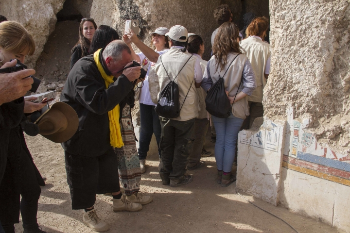 """Tourists photograph an entrance of a newly discovered tomb on Luxor's West Bank known as """"KAMPP 150"""" during an announcement for the Egyptian Ministry of antiquities about new discoveries in Luxor, Egypt, Saturday, Dec. 9, 2017. Egypt's Antiquities Ministry says archaeologists have discovered two ancient tombs in the southern city of Luxor. The ministry said Saturday that one tomb has five entrances leading to a rectangular hall, and contains painted wooden funerary masks, clay vessels and a mummy wrapped in linen. (AP Photo/Hamada Elrasam)"""