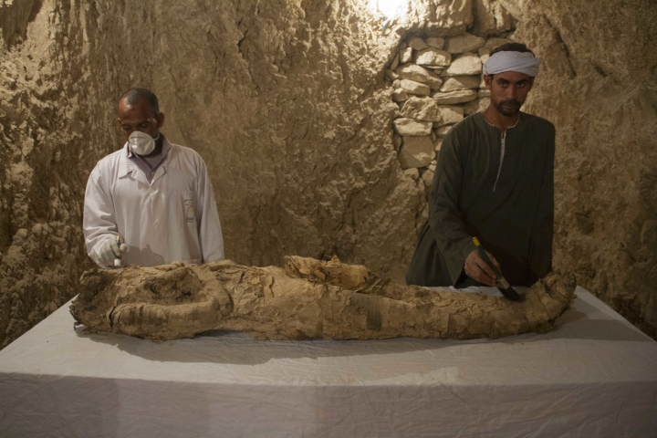 """Egyptian excavation workers restore a mummy in a newly discovered tomb on Luxor's West Bank known as """"KAMPP 150"""" during an announcement for the Egyptian Ministry of antiquities about new discoveries in Luxor, Egypt, Saturday, Dec. 9, 2017. Egypt's Antiquities Ministry says archaeologists have discovered two ancient tombs in the southern city of Luxor. The ministry said Saturday that one tomb has five entrances leading to a rectangular hall, and contains painted wooden funerary masks, clay vessels and a mummy wrapped in linen. (AP Photo/Hamada Elrasam)"""