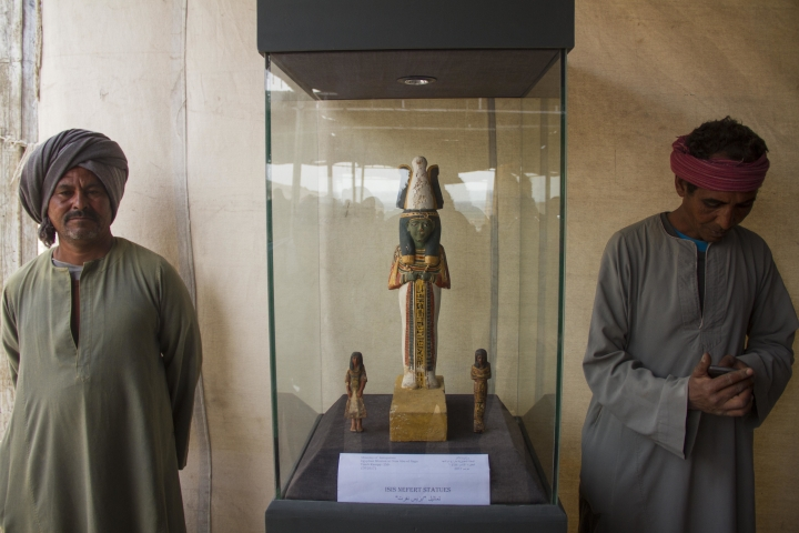 "Egyptian excavation workers guard a wooden statue on display near a new opened tomb known as ""KAMPP 161"" during an announcement for the Egyptian Ministry of antiquities about new discoveries in Luxor, Egypt, Saturday, Dec. 9, 2017. Egypt's Antiquities Ministry says archaeologists have discovered two ancient tombs in the southern city of Luxor. The ministry said Saturday that one tomb has five entrances leading to a rectangular hall, and contains painted wooden funerary masks, clay vessels and a mummy wrapped in linen. (AP Photo/Hamada Elrasam)"