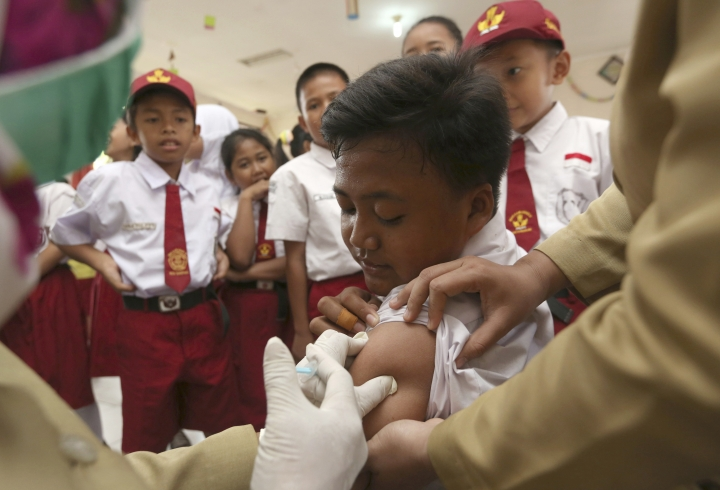 A student receives a diphtheria vaccine at a primary school on the first day of a campaign in Tangerang, Indonesia. Monday, Dec. 11, 2017. Indonesia began a campaign to immunize 8 million children and teenagers against diphtheria. (AP Photo/Tatan Syuflana)
