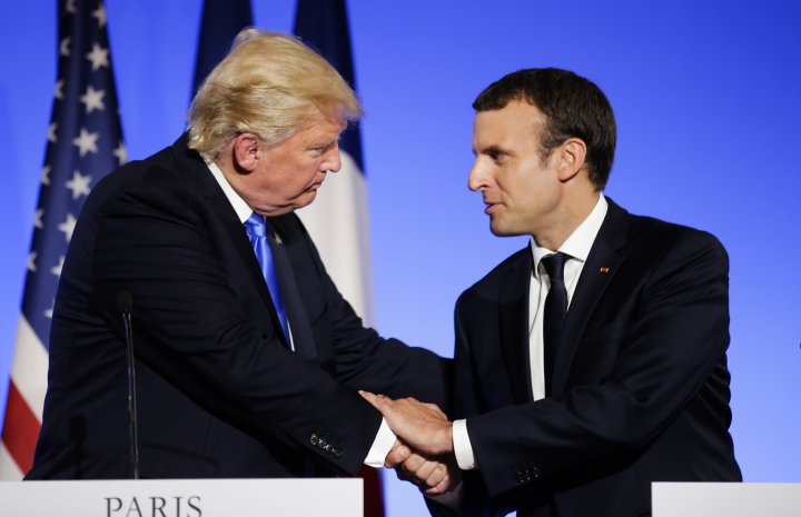 FILE - In this July 13, 2017 file photo, U.S President Donald Trump, left, shakes hands with French President Emmanuel Macron after a press conference at the Elysee Palace in Paris. Macron announced a competition for the grants hours after Trump declared he would withdraw the U.S. from the global accord reached in Paris in 2015 to reduce climate-damaging emissions. Macron is unveiling the winners Monday Dec.11, 2017 evening ahead of a climate summit. (AP Photo/Markus Schreiber, File)