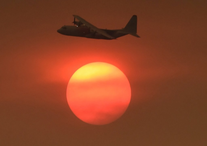 In this photo provided by the Santa Barbara County Fire Department, with smoke obscuring the sun in the distance, a Coulson C-130 Air Tanker turns in to make a drop on a hillside near Toro Canyon Road in Carpinteria, Calif., Monday, Dec. 11, 2017. Ash fell like snow and heavy smoke had residents gasping for air Monday as a wildfire exploded in size, becoming the fifth largest in state history. (Mike Eliason/Santa Barbara County Fire Department via AP)