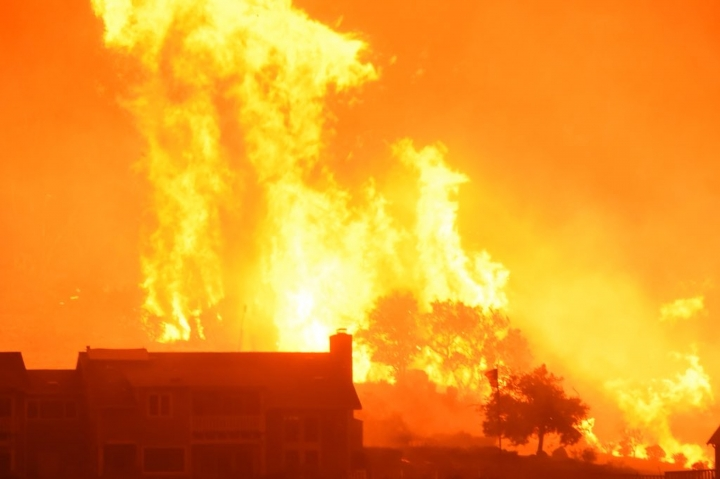 In this Sunday, Dec. 10, 2017 photo released by Santa Barbara County Fire Department, flames advance on homes off Shepard Mesa Road at 5:45 Sunday morning in Carpinteria, Calif. A flare-up on the western edge of Southern California's largest and most destructive wildfire sent residents fleeing Sunday, as wind-fanned flames churned through canyons and down hillsides toward coastal towns. Crews with help from water-dropping aircraft saved several homes as unpredictable gusts sent the blaze churning deeper into foothill areas northwest of Los Angeles that haven't burned in decades. New evacuations were ordered in Carpinteria, a seaside city in Santa Barbara County that has been under fire threat for days. (Mike Eliason/Santa Barbara County Fire Department via AP)