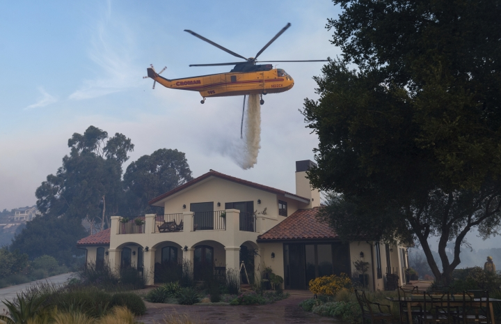 In this Sunday, Dec. 10, 2017, photo a fire-fighting helicopter makes a water drop on a hotspot near a house in the Shepard Mesa neighborhood in Carpinteria, Calif., as a wildfire burns. (Kenneth Song/Santa Barbara News-Press via AP)