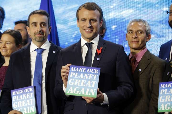 """French President Emmanuel Macron, center, attends the """"Tech for Planet"""" event at the """"Station F"""" start up campus ahead of the One Planet Summit in Paris, France, Monday Dec. 11, 2017. It is a dream come true for U.S.-based climate scientists — the offer of all-expenses-paid life in France to advance their research in Europe instead of in the United States under climate skeptic President Donald Trump, two of the winners say. (Philippe Wojazer, Pool via AP)"""