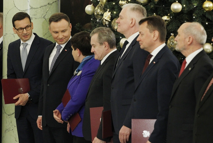 Poland's President Andrzej Duda, second left, hands new Prime Minister Mateusz Morawiecki, left, and Beata Szydlo talk during a ceremony at the Presidential Palace in Warsaw, Poland, Monday, Dec. 11, 2017. Morawiecki is to focus on developing Poland's economy and improving the government's image abroad. (AP Photo/Czarek Sokolowski)