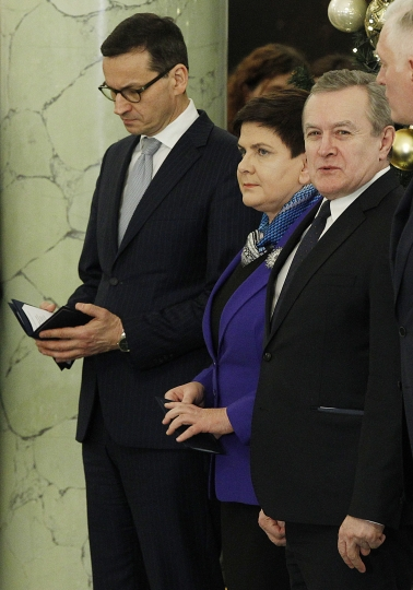 Polish new Prime Minister Mateusz Morawiecki, left, and Beata Szydlo, second left, talking during a ceremony at the Presidential Palace in Warsaw, Poland, Monday, Dec. 11, 2017. Morawiecki is to focus on developing Poland's economy and improving the government's image abroad. (AP Photo/Czarek Sokolowski)