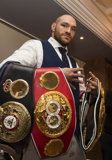 FILE - In this file photo dated Monday, Nov. 30, 2015, newly crowned heavyweight world boxing champion Tyson Fury poses for photographs in Bolton, England, Monday, Nov. 30, 2015, after defeating 39-year-old Ukrainian Wladimir Klitschko in Dusseldorf, Germany on Saturday to become the WBA, IBF and WBO heavyweight champion. It is announced Tuesday Dec. 12, 2017, that Tyson Fury is free to box again after receiving a backdated two-year ban for an anti-doping violation. Fury has not fought since beating Wladimir Klitschko in November 2015. (AP Photo/Jon Super, FILE)