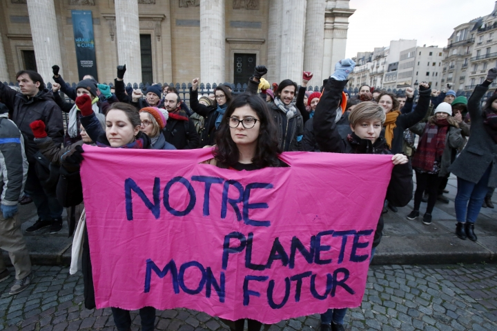 An environmental activist displays a placard as she protests at Pantheon monument in support of the Paris climate accord, in Paris, France, Tuesday, Dec. 12, 2017. Placard reads : Our Planet My Future. More than 50 world leaders are gathering in Paris for a summit that President Emmanuel Macron hopes gives new momentum to the fight against global warming despite U.S. President Donald Trump's rejection of the Paris climate accord. (AP Photo/Michel Euler)
