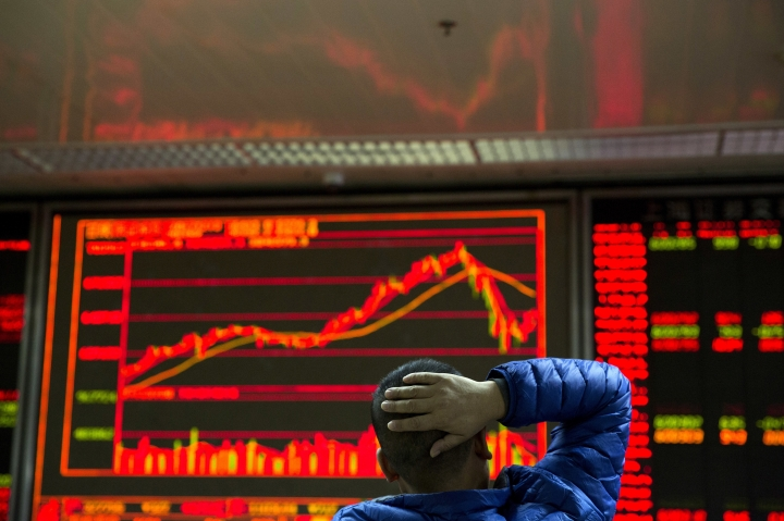 An investor looks at the Chinese market index at a brokerage in Beijing, China, Wednesday, Dec. 13, 2017. Asian stocks were mixed Wednesday following overnight gains on Wall Street as investors looked ahead to a likely U.S. interest rate hike. (AP Photo/Ng Han Guan)