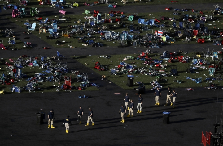 FILE - In this Tuesday, Oct. 3, 2017, file photo, investigators work at a festival grounds across the street from the Mandalay Bay Resort and Casino in Las Vegas, where two days earlier a gunman began firing with a cache of weapons, killing dozens and injuring hundreds at a music festival. The shooting was one of the top searches on Google in 2017. (AP Photo/Marcio Jose Sanchez, File)