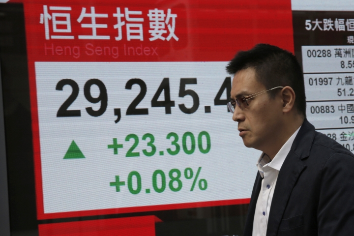 A man walks past an electronic stock board showing the Hang Seng Index at a bank in Hong Kong, Thursday, Dec. 14, 2017. Asian stocks were mixed on Thursday after the Fed raised rates again, meeting investor expectations but providing few surprises. (AP Photo/Kin Cheung)