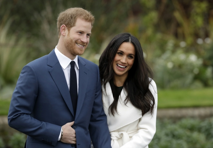 FILE - In this Monday Nov. 27, 2017 file photo, Britain's Prince Harry and his fiancee Meghan Markle pose for photographers during a photocall in the grounds of Kensington Palace in London. Prince Harry and Meghan Markle to marry on May 19, 2018. (AP Photo/Matt Dunham)