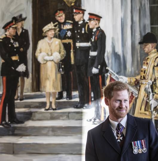 """Britain's Prince Harry stands beneath a painting of himself and Prince William when they were Sandhurst cadets with Queen Elizabeth and other members of the royal family, that hangs in the entrance to """"Old college"""", during the Sovereign's Parade at The Royal Military Academy Sandhurst in Sandhurst, England, Friday, Dec. 15, 2017. Prince Harry and Meghan Markle will marry on May 19 in St. George's Chapel at Windsor Castle, Kensington Palace announced Friday. (Richard Pohle/Pool Photo via AP)"""