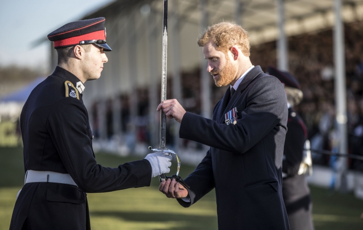Britain's Prince Harry presents the sword of honour to the best overall officer cadet during the Sovereign's Parade at The Royal Military Academy Sandhurst in Sandhurst, England, Friday, Dec. 15, 2017. Prince Harry and Meghan Markle will marry on May 19 in St. George's Chapel at Windsor Castle, Kensington Palace announced Friday. (Richard Pohle/Pool Photo via AP)