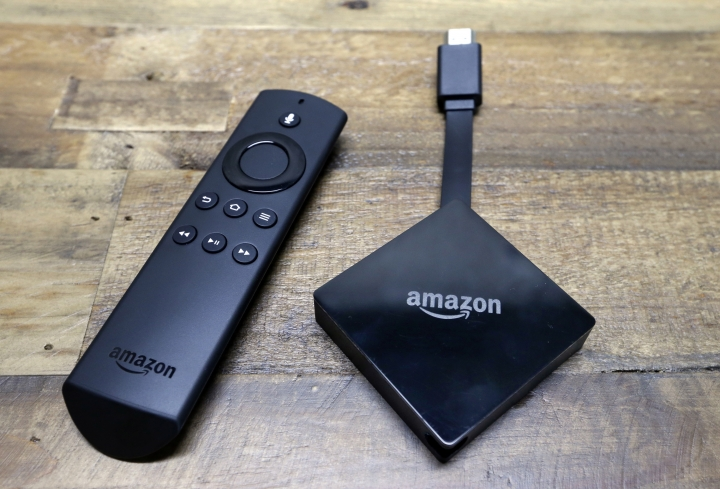FILE - This Sept. 27, 2017, file photo, shows an Amazon Fire TV streaming device displayed with its remote. The device plugs into the back or side of a television set to stream Netflix and other video. Amazon is angling for a truce in its two-year battle with Apple and Google over streaming gadgets: It says it is preparing to put Apple TV and Chromecast back on sale. A spokeswoman for Amazon confirmed Friday, Dec. 15, 2017, it is preparing to sell the devices. Links to the products appeared on Amazon.com but indicate they are still unavailable. (AP Photo/Elaine Thompson, File)