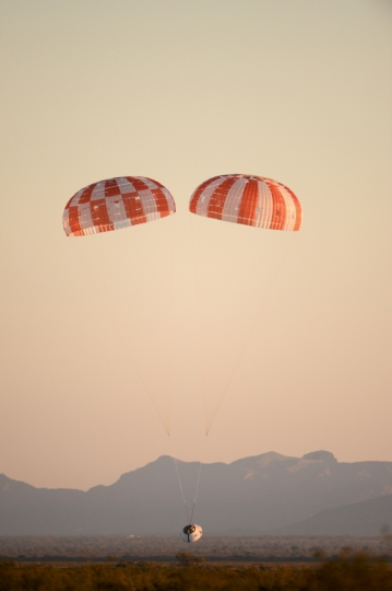 This photo released by NASA shows a replica Orion Spacecraft dropped from a U.S. Air Force C-17 transport aircraft at 35,000 feet in altitude to a southwestern Arizona desert site to test the craft's ability to cope with a partial parachute failure at the U.S. Army Proving Ground in Yuma, Ariz., Friday, Dec. 15, 2017. The test used two of Orion's three main parachutes to simulate the failure of the third and still sufficiently slowed the spacecraft for a landing. It was the fifth of eight tests to qualify Orion's parachute system for flights with astronauts beginning with Exploration Mission-2. (U.S. Army/NASA via AP)