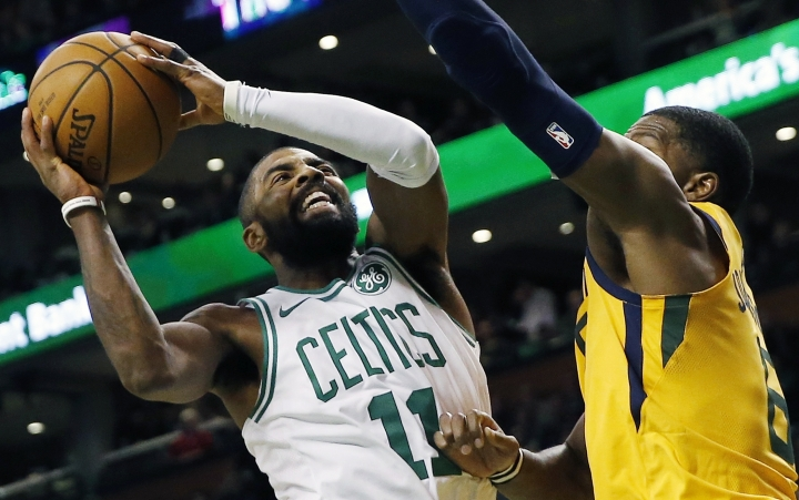 Boston Celtics' Kyrie Irving (11) shoots against Utah Jazz's Joe Johnson (6) during the third quarter of an NBA basketball game in Boston, Friday, Dec. 15, 2017. (AP Photo/Michael Dwyer)