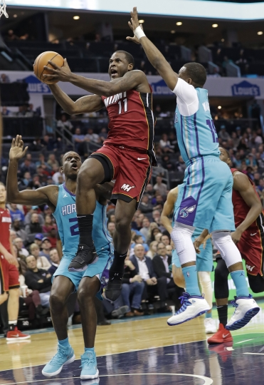 Miami Heat's Dion Waiters (11) drives between Charlotte Hornets' Treveon Graham (21) and Kemba Walker (15) during the second half of an NBA basketball game in Charlotte, N.C., Friday, Dec. 15, 2017. (AP Photo/Chuck Burton)