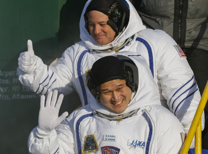 U.S. astronaut Scott Tingle, above, and Japanese astronaut Norishige Kanai, crew members of the mission to the International Space Station, ISS, wave near the rocket prior to the launch of Soyuz-FG rocket at the Russian leased Baikonur cosmodrome, Kazakhstan, Sunday, Dec. 17, 2017. (AP Photo/Shamil Zhumatov, Pool)