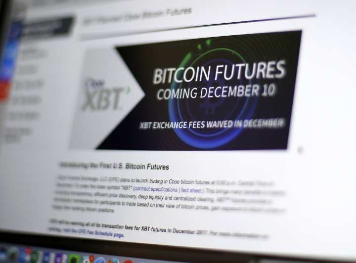 FILE - This Dec. 8, 2017, file photo shows the Chicago Board Options Exchange website announcing that bitcoin futures will start trading on the Cboe on Sunday evening Dec. 10. The CME Group, another security based on the price of bitcoin, the digital currency that has soared in value and volatility this year, began trading on the Chicago Mercantile Exchange on Sunday, Dec. 17. (AP Photo/Kiichiro Sato, File)