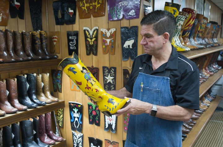 Duane Little holds a custom designed yellow kangaroo skinned cowboy boots made by his family's shop, Little's Boot Company, Wednesday Sept. 20, 2017, in San Antonio, Texas. (AP Photo/Marco Garcia)