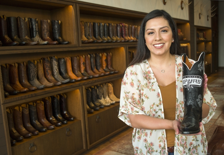 Lucchese saleswoman Michelle Esquivel holds a pair of custom made cowboy boots at the Lucchese Boot Maker shop, Wednesday Sept. 20, 2017, in San Antonio, Texas. The Lucchese store sells off the shelf hand crafted boots made in Texas. (AP Photo/Marco Garcia)