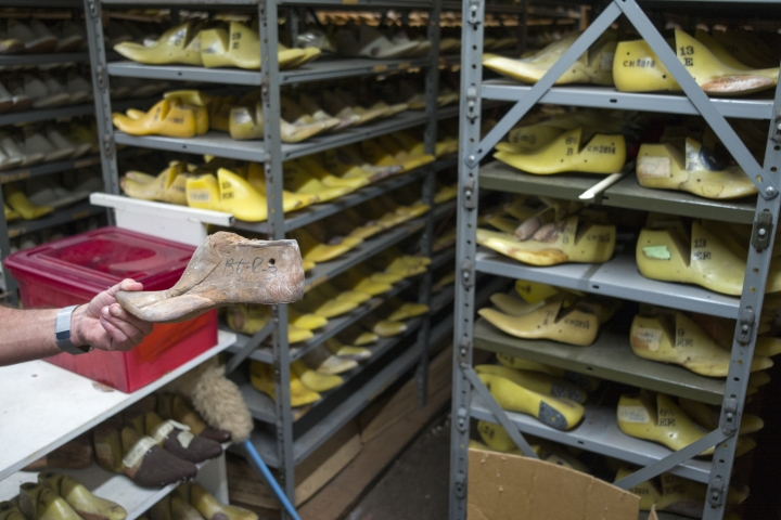 While standing in store room holding hundreds of custom shaped foot lasts, or foot molds, Duane Little holds a custom last of made for a customer at Little's Boot Company, Wednesday Sept. 20, 2017, in San Antonio, Texas. Cowboy boots created by Little's start with a customer having their feet measured and a custom mold designed specifically for them. Little's keeps the molds and customers can order boots anytime after their initial measurements are taken. Little said many lasts in their workshop go back decades. (AP Photo/Marco Garcia)
