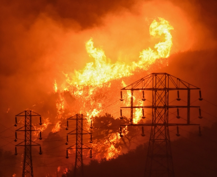 In this Saturday, Dec. 16, 2017, photo provided by the Santa Barbara County Fire Department, flames burn near power lines in Sycamore Canyon near West Mountain Drive in Montecito, Calif. One of the largest wildfires in California history is now 40 percent contained but flames still threaten coastal communities as dry, gusty winds are predicted to continue. Some 8,000 firefighters are deployed to the so-called Thomas Fire, which has burned for nearly two weeks and still threatens 18,000 homes. Swaths of Santa Barbara County remain under evacuation orders. (Mike Eliason/Santa Barbara County Fire Department via AP)