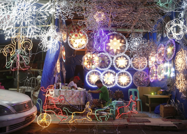 """In this Dec. 9, 2017, photo, lantern makers work on traditional Christmas lanterns locally known as """"parols"""" in a side street shop in Manila, Philippines. These small lanterns traditionally decorate many Filipino homes during the Christmas holidays. (AP Photo/Iya Forbes)"""