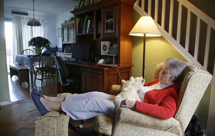 "In this Friday Dec. 1, 2017, photo, 93-year-old Mary Derr sits with her robot cat she calls ""Buddy"" in her home she shares with her daughter Jeanne Elliott in South Kingstown, R.I. (AP Photo/Stephan Savoia)"