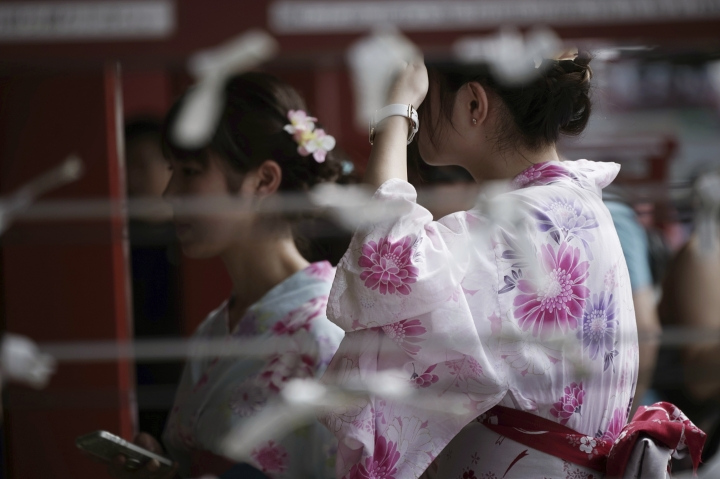 """FILE - In this Aug. 22, 2017, file photo, visitors wearing a traditional Japanese summer kimono or """"yukata"""" stroll through a temple in Tokyo. U.S. visitors to Japan increased 10 percent January through October 2017 compared to the same period in 2016, and the upward trend is expected to continue through 2018 as Japan heads toward the 2020 Summer Olympics. (AP Photo/Eugene Hoshiko, File)"""