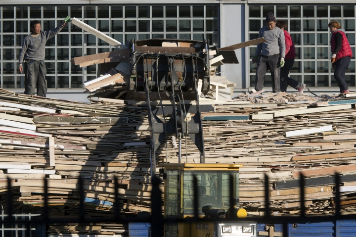 Workers collect wooden planks for recycling outside an exhibition center in Beijing, China, Wednesday, Dec. 20, 2017. Chinese leaders have promised to increase imports and reduce risks in their financial system following an annual planning meeting amid slowing economic growth and pressure from trading partners to open their markets wider. (AP Photo/Ng Han Guan)