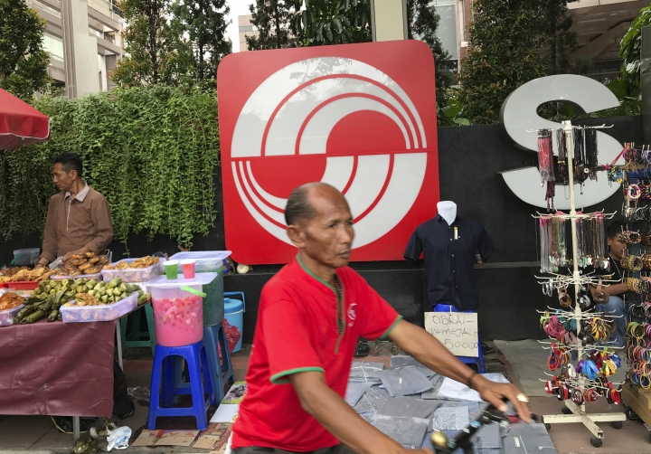 In this Oct. 1, 2017, photo, a man rides a bicycle past the Sinarmas logo installed outside of the Sinarmas Land Plaza during a car-free day in the main business district of Jakarta, Indonesia. Despite its denials, Sinarmas, one of the world's biggest paper producers, has extensive behind-the-scenes ties and significant influence over wood suppliers linked to fires and deforestation that have degraded Indonesia's stunning natural environment. (AP Photo/Dita Alangkara)