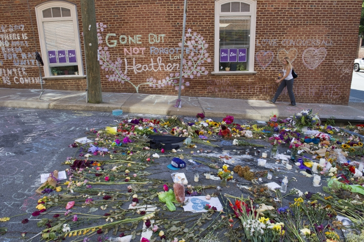 FILE- This Aug. 18, 2017 file photo shows a woman walking through the memorial at the site where Heather Heyer was killed in Charlottesville, Va. Heyer was struck and killed by a car while protesting a white nationalist rally on Aug. 12. The city of Charlottesville is preparing to dedicate a downtown street in her honor. (AP Photo/Cliff Owen, File)