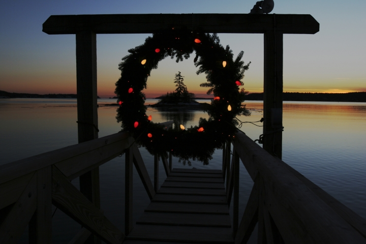 FILE - This Tuesday, Dec. 18, 2007 file photo shows a Christmas wreath decorated with lights at the end of a dock at sunset on Linekin Bay in East Boothbay, Maine. Wintertime can trigger true but transient depression in some people, a condition sometimes called Seasonal Affective Disorder. It's linked with lack of sunlight in winter and some scientists think affected people overproduce the sleep-regulating hormone melatonin. Research suggests it affects about 6 percent of the U.S. population and rates are higher in Scandinavia. But contrary to popular belief, suicides peak in springtime, not winter. No one has figured out why. (AP Photo/Pat Wellenbach)