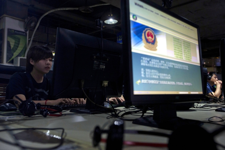 FILE - In this Aug. 19, 2013, file photo, computer users sit near a monitor display with a message from the Chinese police on the proper use of the Internet at an Internet cafe in Beijing. A Chinese official newspaper says an entrepreneur has been sentenced to 5 ½ years in prison in December 2017 for selling virtual private network service amid a campaign by Beijing to stamp out technology that evades its internet filters. (AP Photo/Ng Han Guan, File)
